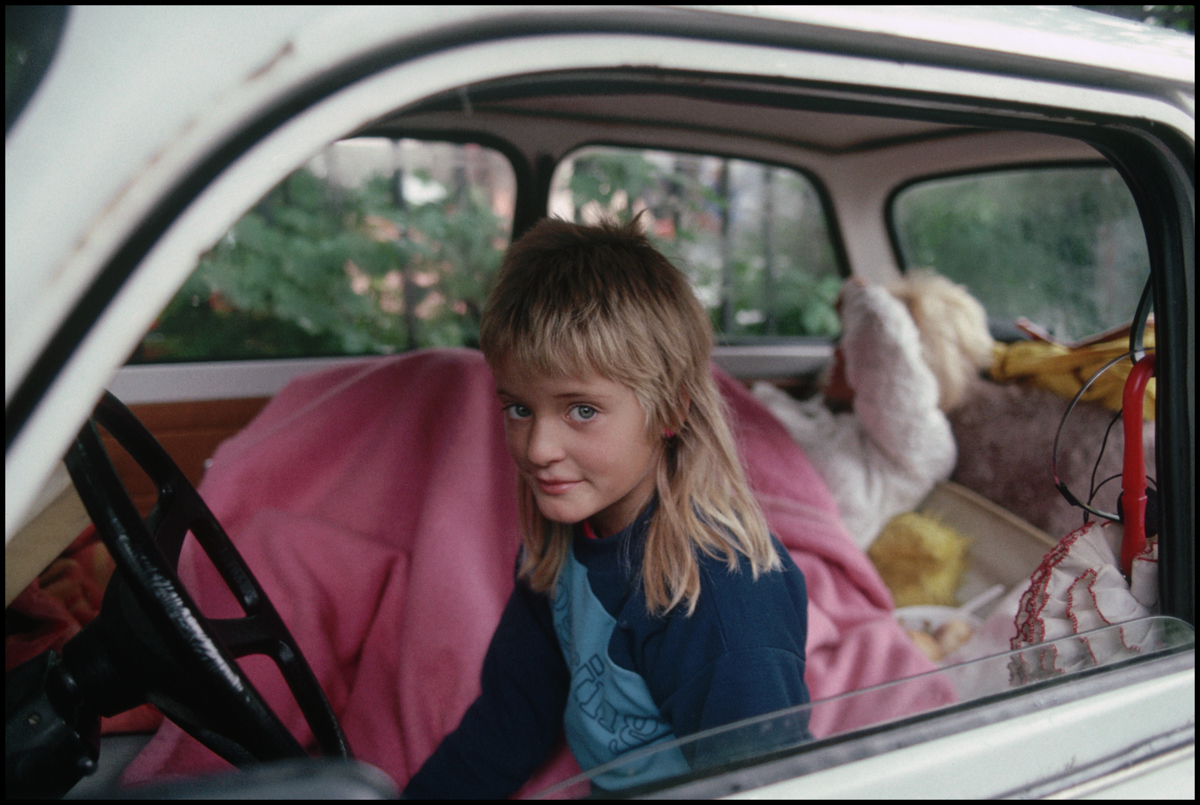 ca. 1989, Budapest, Hungary --- A young East German girl sits behind the steering wheel of her family's car.