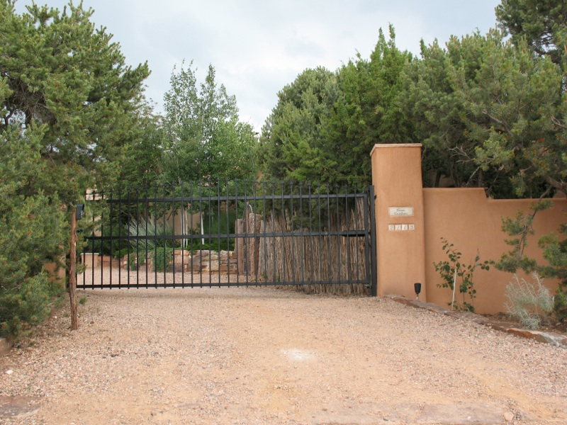 Automatic access system controlling wrought iron gate, with wall and coyote fence