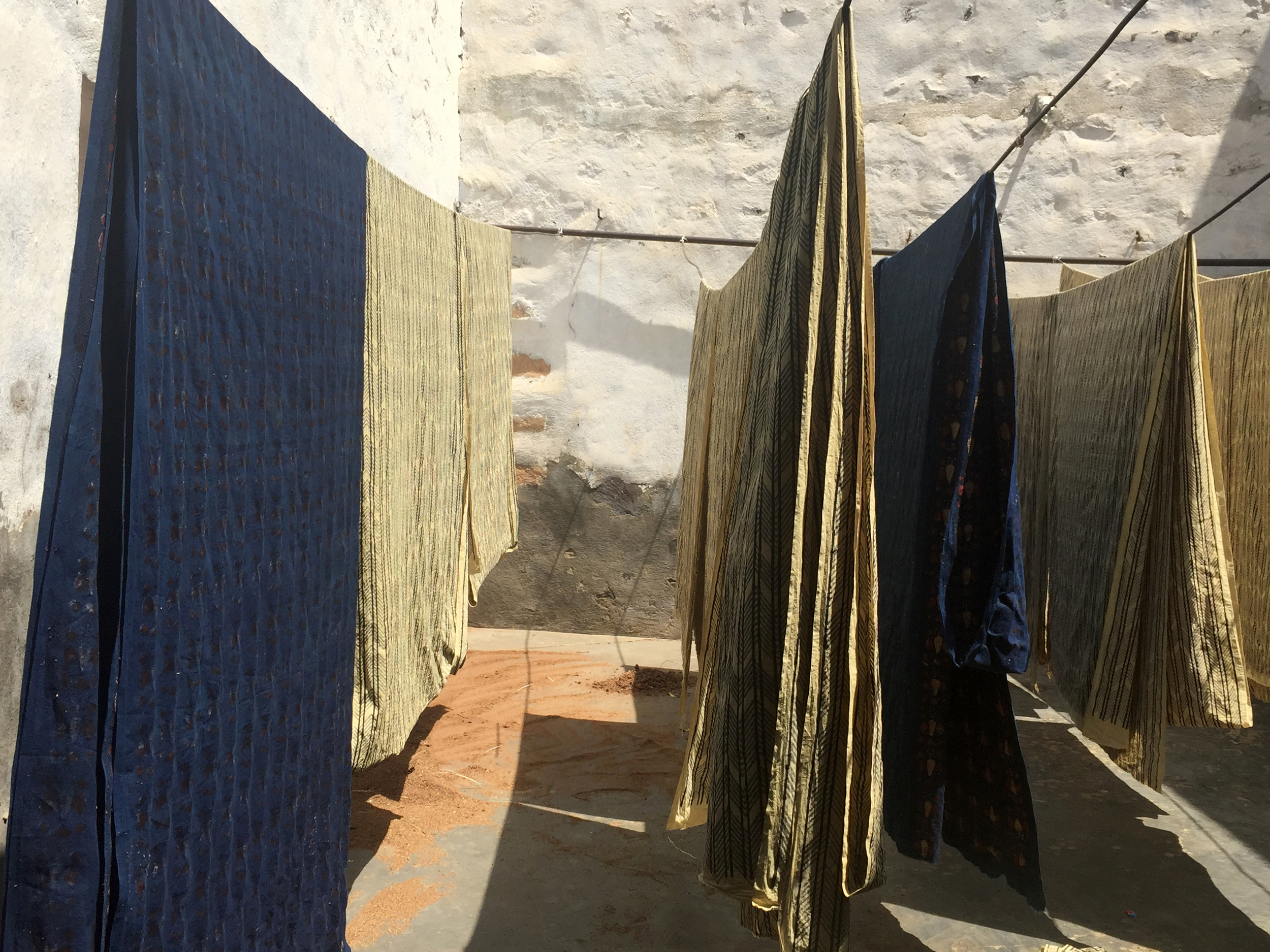Having read about a 5th generation family of Indigo-dye block printers in a small town in northwest India, in the Fall of 2015 we set out on a bumpy 3-hour drive with three brothers' first names but no address. We stopped at several tea vendors until one was able to point us down a dirt lane to a small house of natural dyers. There we witnessed the entire family, spanning several generations, quickly and precisely dipping hand-carved blocks into indigo dye baths, stamping yards of fabric and hanging them to dry in the small courtyard out back.  We have been working with this family ever since to develop beautiful natural-dyed block-printed designs to incorporate into our collection for IMMODEST COTTON. To create the block printed fabrics that we use in IMMODEST COTTON, the cotton is first printed by hand using a mud-based resist-paste, then dyed using natural indigo, revealing the pattern in white. This technique requires time, practice and patience, and is both a scientific and artistic endeavor. It results in unique variations within the print, enriching the character of each product.