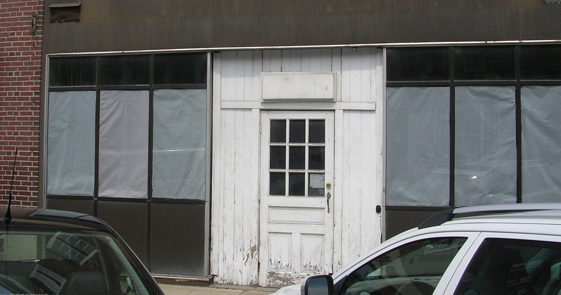 The Windham   Coffee Shop facade as it was   'remuddled' sometime after 1966 with plywood, aluminum and plate glass. The remuddled modernization was removed in 2009, exposing precious few of the original facade architectural elements. Fortunately, enough detail was uncovered to allow the original facade to be accurately replicated. See below.