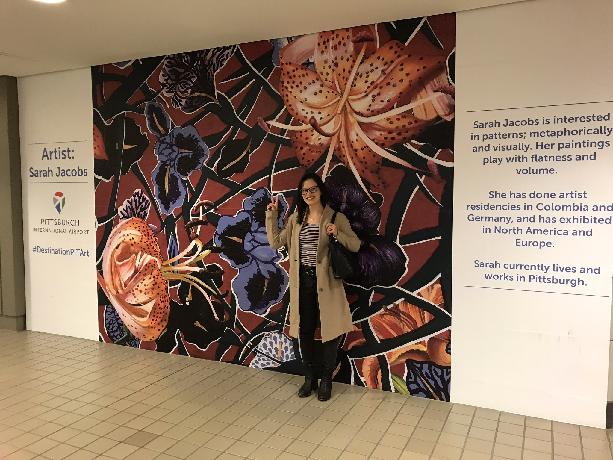 Sarah Jacobs with a large-scale reproduction of her painting, Fake Flowers, at the Pittsburgh International Airport, 2019