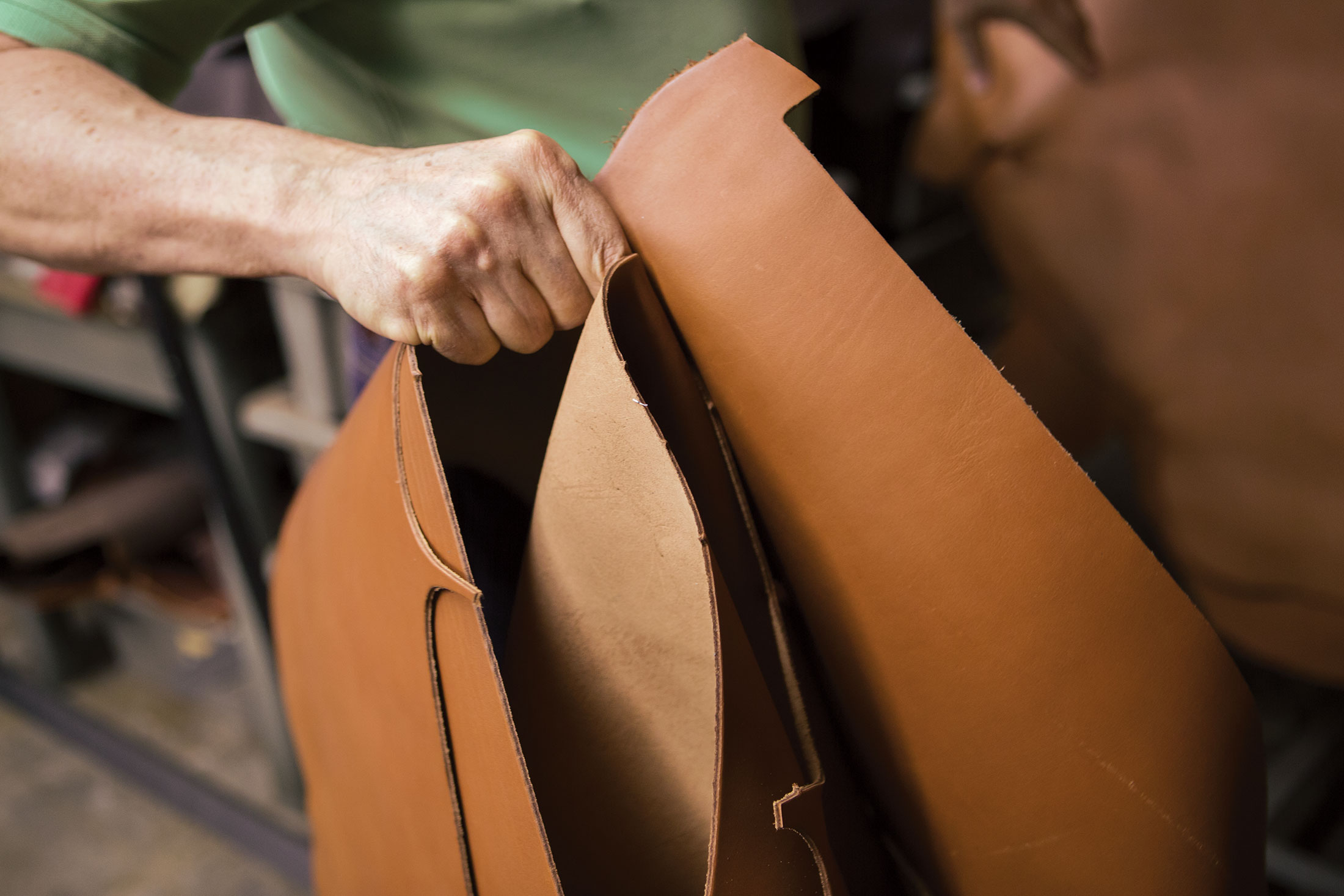 A craftsperson handling cut leather pieces.