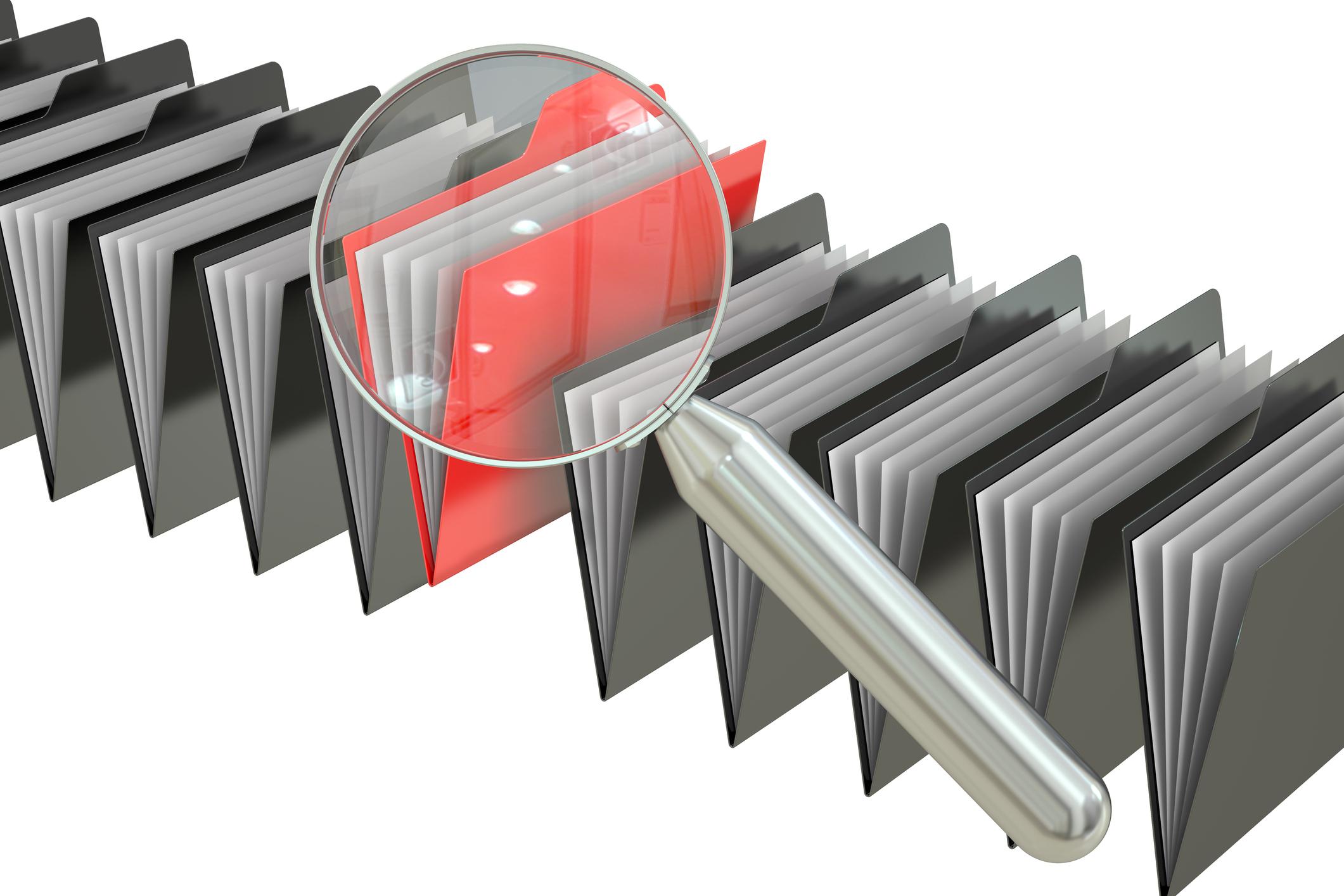 Magnifying glass over red file folder.jpg