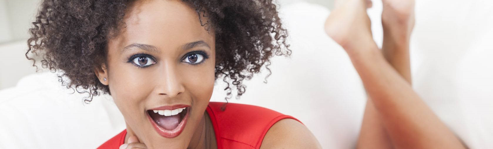 A-beautiful-mixed-race-African-American-girl-or-young-woman-laying-down-wearing-a-red-dress-looking-happy-and-surprised-.jpg