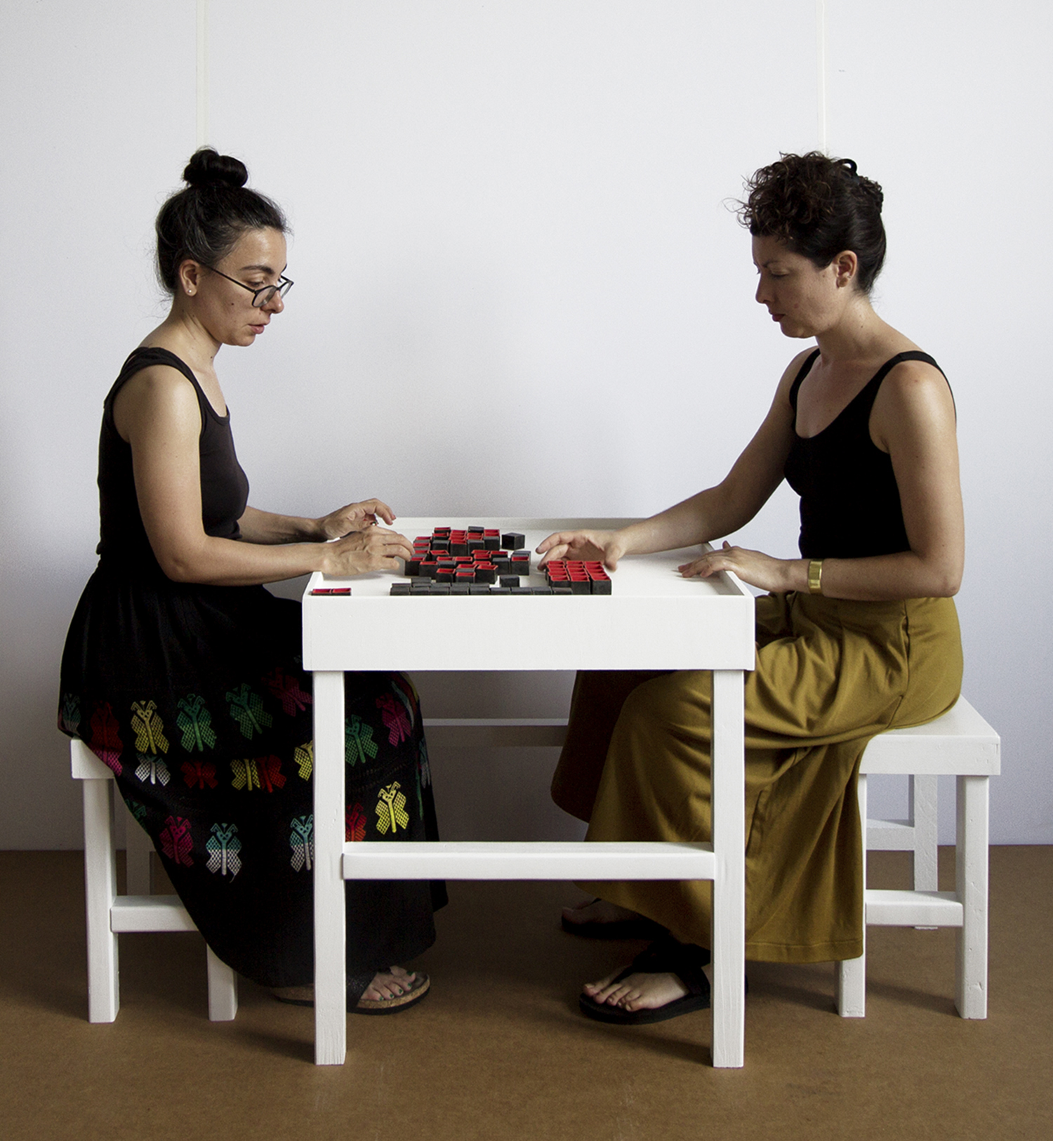 Invitation to Play : Open | Close | Open , interactive installation at the Bronx Museum of the Arts, July 22 - October 22, 2017  79 small ceramic vessels constitute game pieces in a moveable grid, representing organs in the human body. The title is lifted from a poem by Israeli poet Yehuda Amichai that reflects on states of being open/closed/open during pre-birth/life/death, respectively. During Performance sessions I invite visitors to play with me. They make the first move and determine the length of the game. The game has no rules.    Excerpts from these interactions: