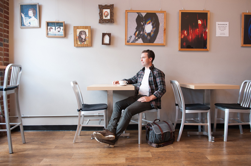 Cliff enjoying a cup of coffee. Artwork by the Kuriosity Lab and Bliss barista Anna Kachelries hang behind him.