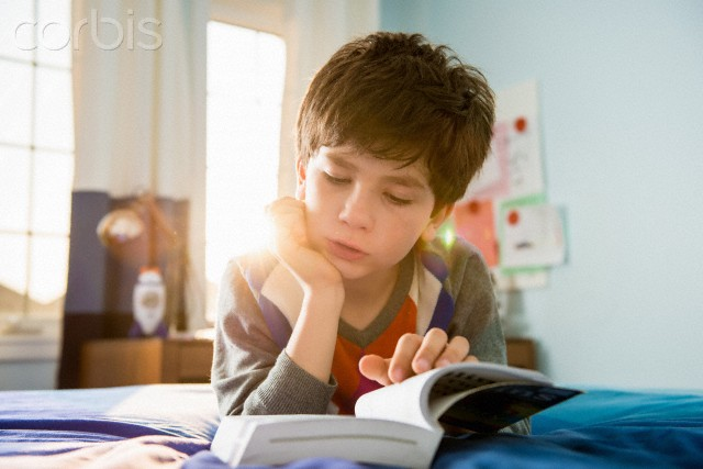 Corbis-42-52269534 boy lying on bed reading.jpg