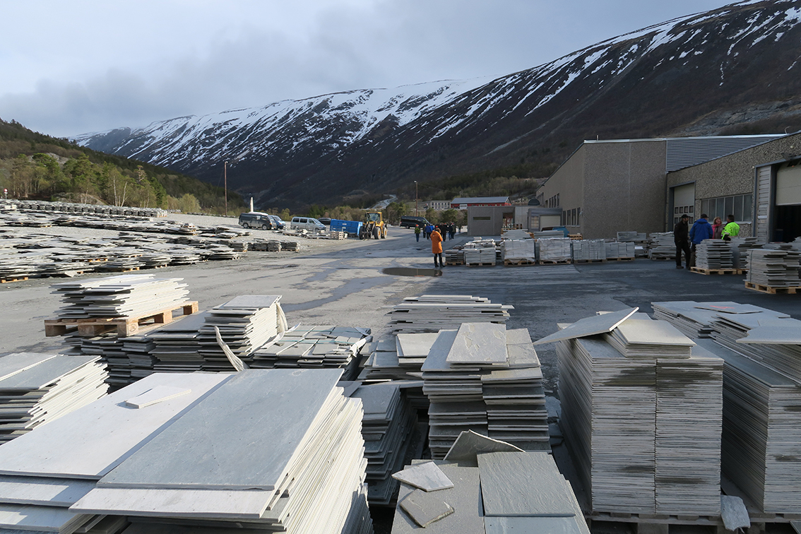 """Fra befaringen på hovedanlegget til Minera Skifer. Bedriften opplyser følgende på sin nettside:  """"Minera Skifer representerer skiferprodukter med høy kvalitet fra skandinaviske bergarter, som er mange hundre millioner år gamle. Minera Skifer er Skandinavias ledende skiferprodusent og har skiferbrudd i Oppdal og Otta i Norge og i Offerdal i Sverige.Hovedkontoret er lokalisert på Oppdal.Minera Skifer- konsernet har ca 145 ansatte og produserer knapt 300 000 m 2 årlig. Årlig salg er ca. NOK 160 mill.Skifer fra Minera Skifer er eksportert til alle verdensdeler, og har gjennom årtier opparbeidet et godt rykte som kvalitetsprodukter. Alle produktene er CE-merket"""". Foto: A. Nyaas     Dyktige guider på bussturen rundt om i Oppdal, var Lars Rise og Narve Hårstad, for øvrig leder og nestleder i Oppdal Bygdelamenning"""