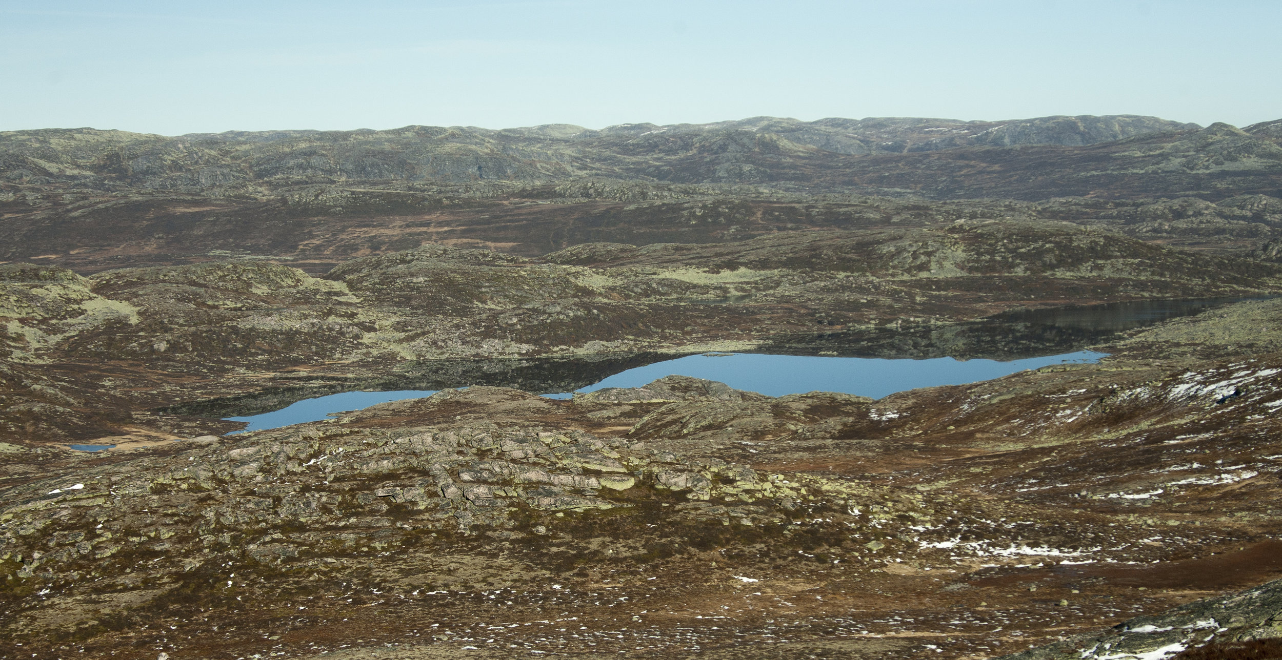 Dette er innsjøen Vesle Saure sett mot nord. Me ser Vråsjåhallene som ei mørkare flate litt bak i øvre del av biletet. Heilt til venstre i biletet, opp frå vatnet og til venstre ligg ryggen der lynet har slege ned, i nordhallet av denne skjedde det.Foto: Kjell Bitustøyl