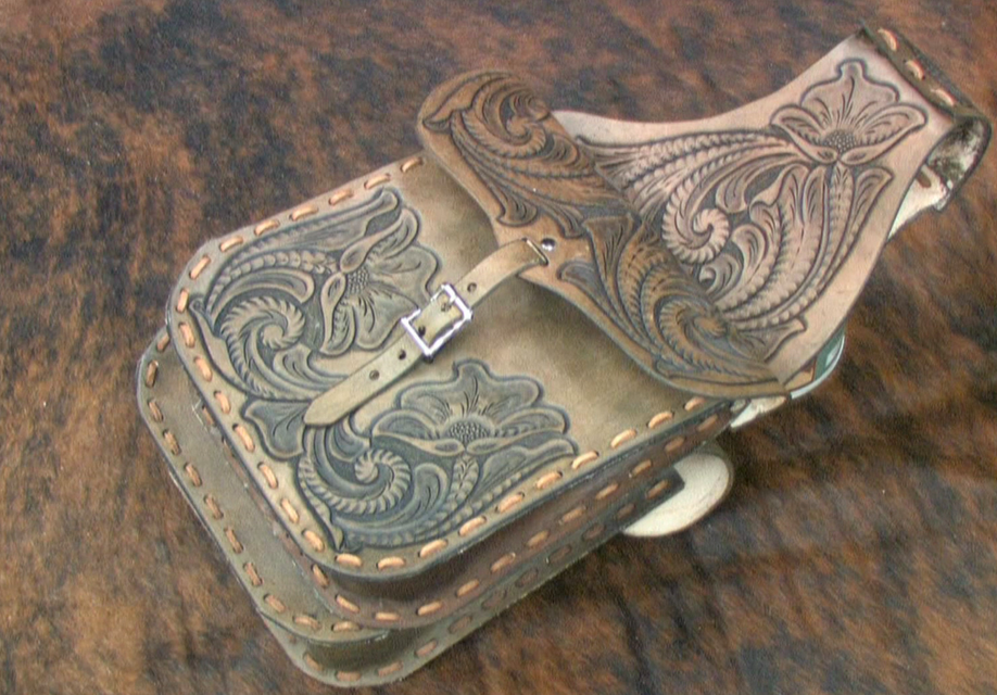 Source: Tandy Leather Factory. A native American rawhide saddlebag was flat like an envelope, decorated with patterns and long fringes. A cowboy's bag was plain with a buckle flap.