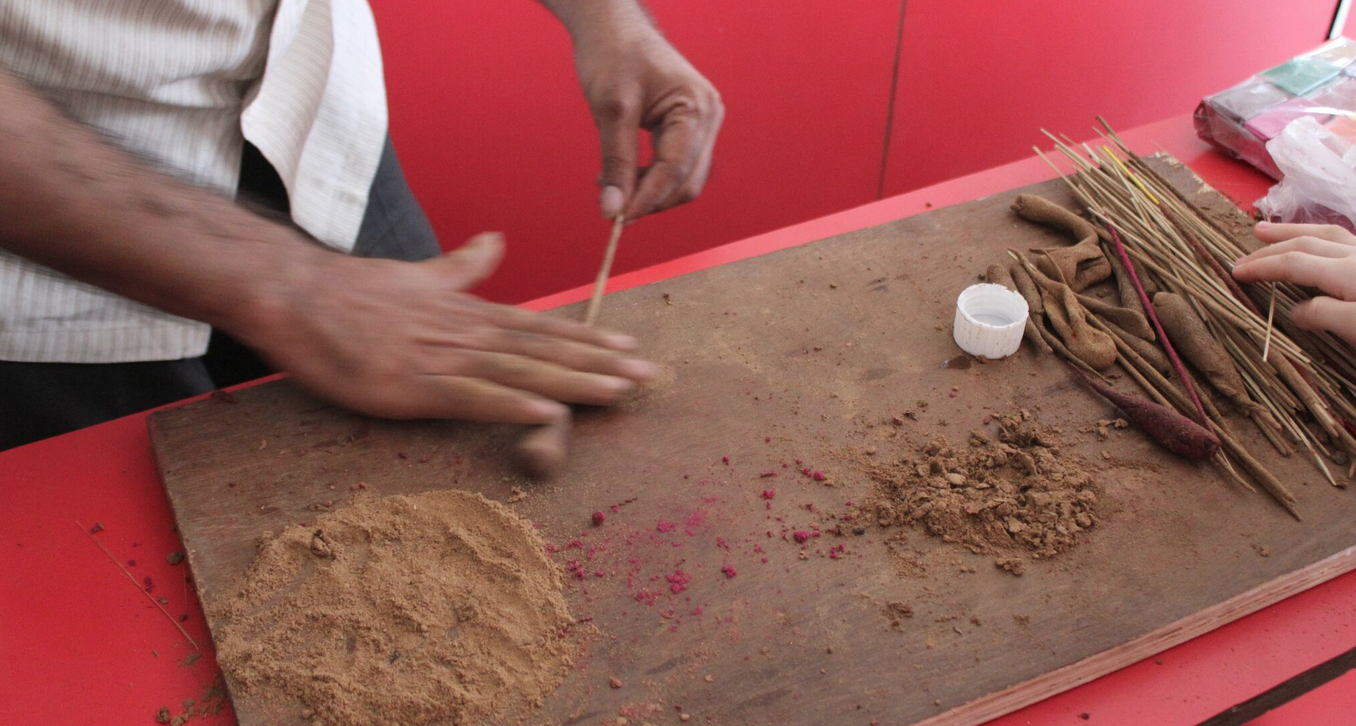 Hand rolling joss sticks in Fort Kochi; fragrant powders mixed to order