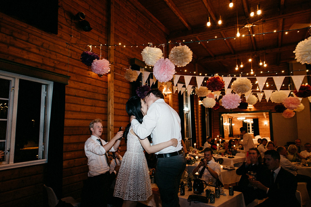 Wedding couple kisses standing  on chairs