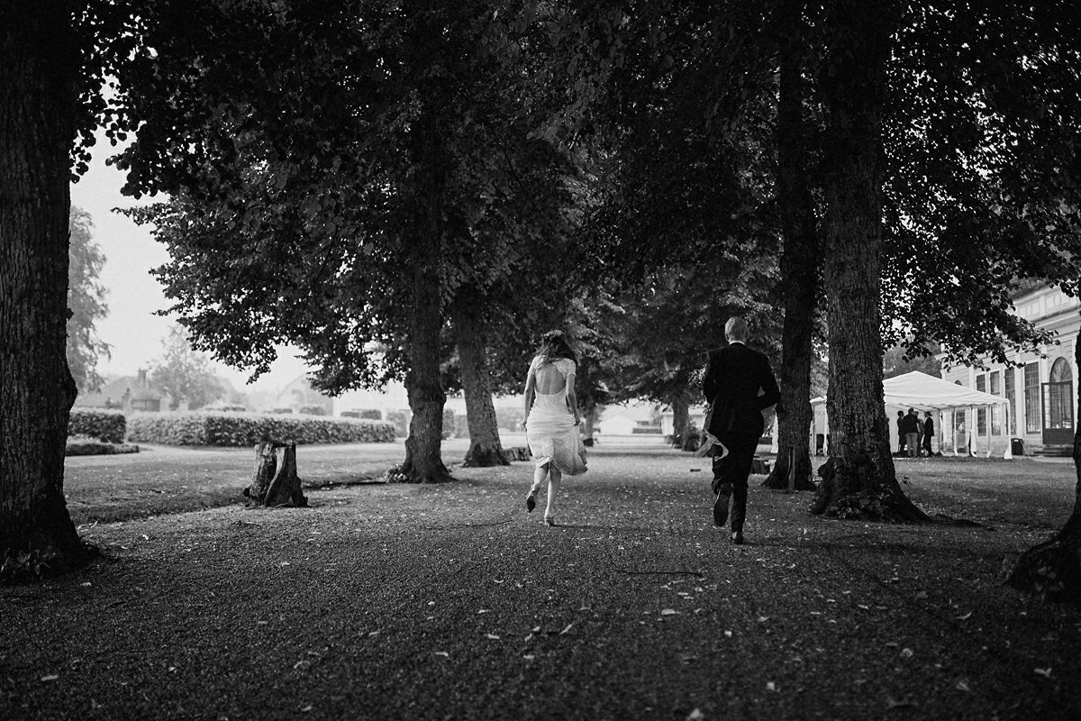 Bride and groom runs for cover from the rain