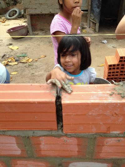 A young family member helping with the construction of her new house.