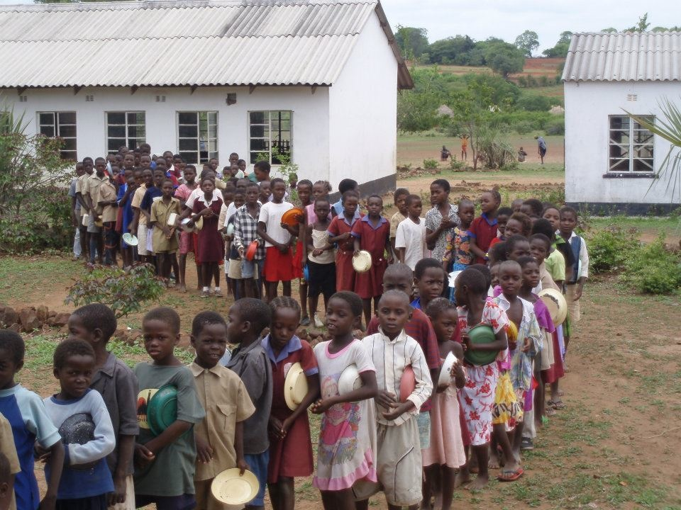 Students wait in line for their daily donated lunch which is part of our Feed Program. It's often these kids go hungry and don't have the energy to walk to school. The food program has helped enormously with attendance rates, as well as school performance and grades. A typical meal is Sadza (cornmeal), beans and a vegetable (generally spinach).