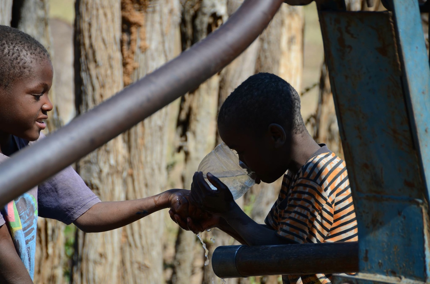 On a hot day, young brothers stop by for a cool drink before watering the livestock that they attend to for their community. These wells are a water source for both the community and animals.