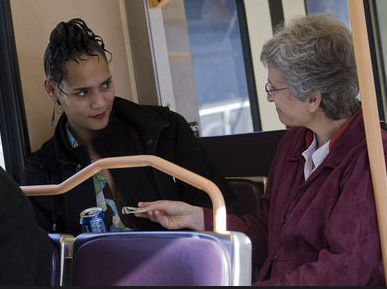 Jill Ginsberg gives $100 to a stranger on a Portland bus. Bruce Ely photograph, The Oregonian.