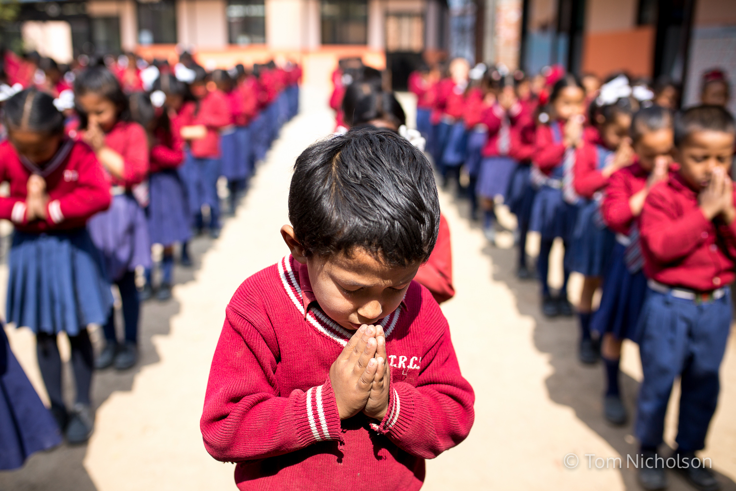 A young boy prays during assembly at the Tri Ratna Cooperative School, also known as Bungamati School in Bungamati District, Kathmandu, Nepal on 15 March 2016. The school and surrounding village were devastated in the April 2015 earthquake.