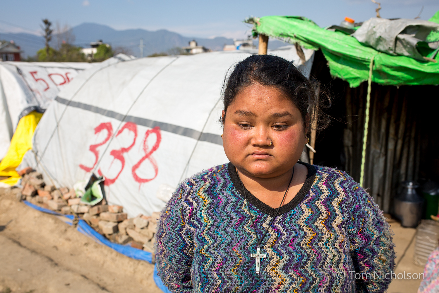 Susmita (15) in the Internally Displaced Person (IDP) camp in Chuchepati, Kathmandu City, Nepal on 16 March 2016. Susmita is blind due to meningitis, diagnosed in 2012, (when she was 11). She lives in the tent with her grandmother, mother, father, and five younger siblings. They moved to the camp on 12 May 2015 following the April 2015 earthquake.