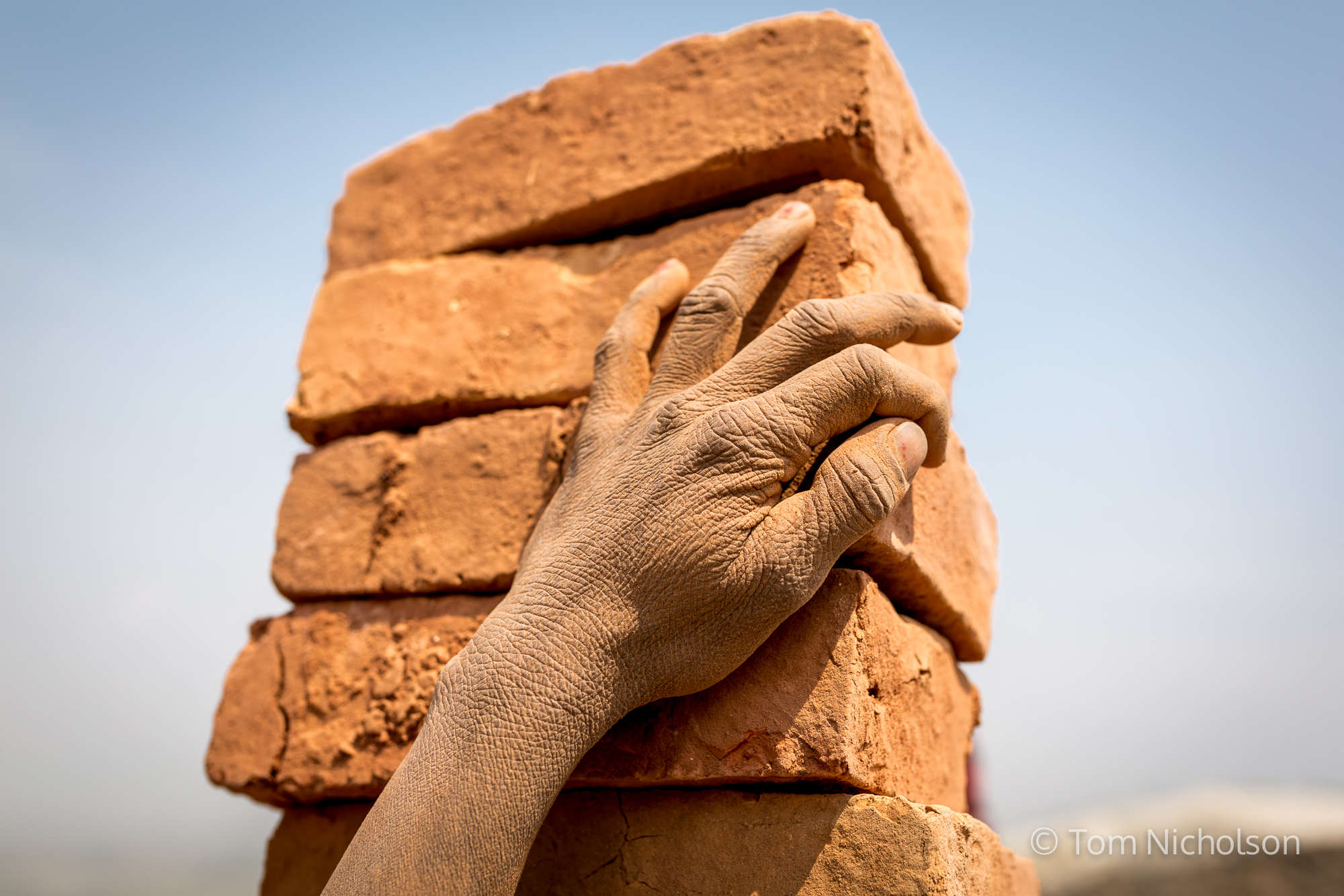 An Indian migrant worker carries bricks in the UK brickworks factory in Bungamati, Kathmandu, Nepal on 15 March 2016. Around 400 labourers, including children, work in very dusty and hot conditions.