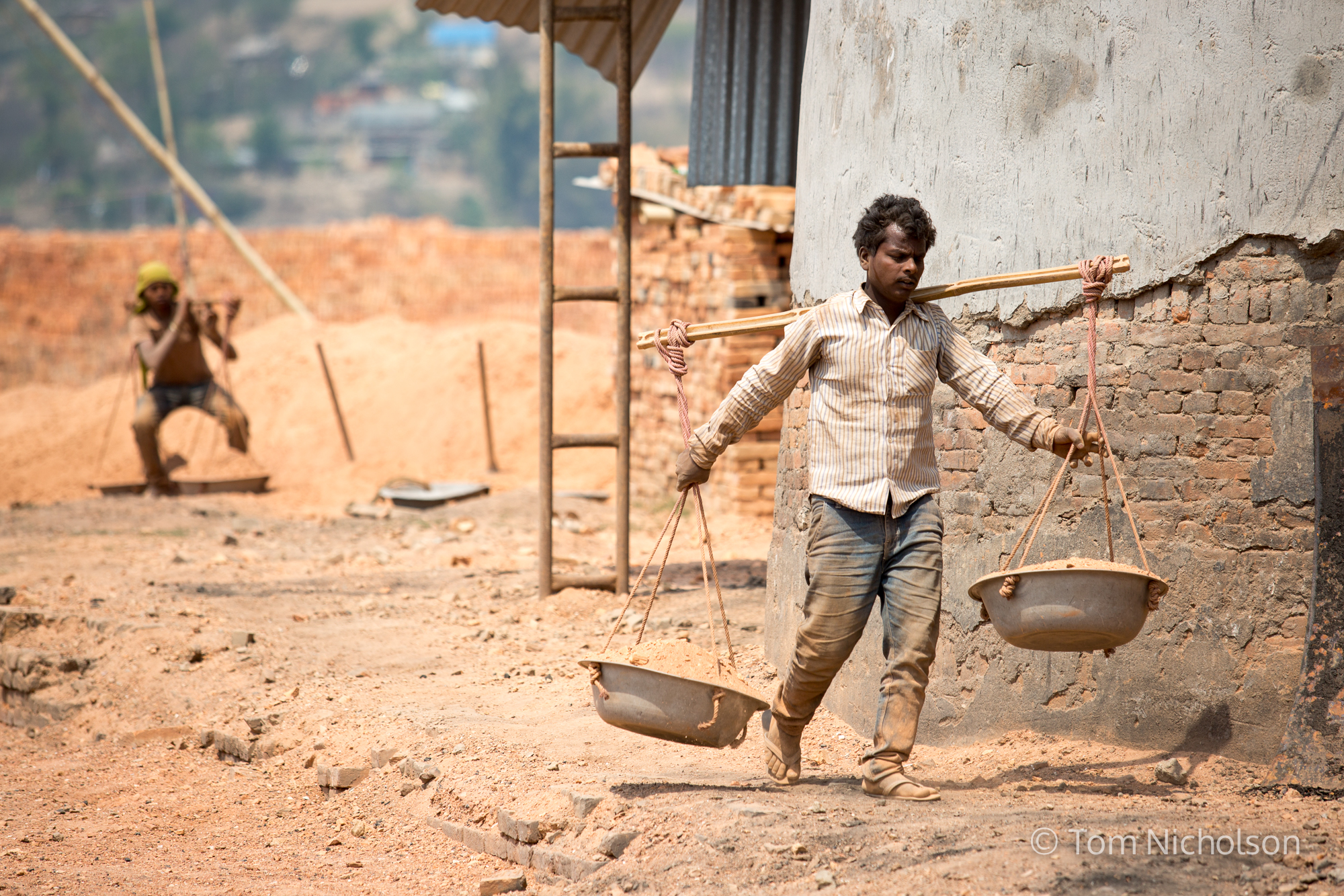 Labourers carry sand in the UK brickworks factory in Bungamati, Kathmandu, Nepal on 15 March 2016. Around 400 labourers, including children, work in very dusty and hot conditions.