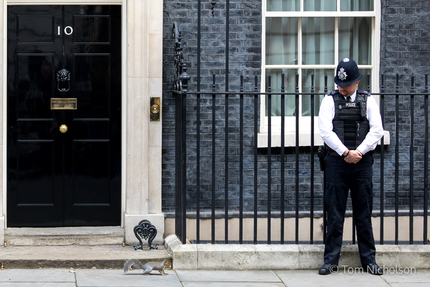 ©2017 Tom Nicholson. 26/09/2017. London, UK. A policeman looks as a squirrel runs past No 10 Downing Street.
