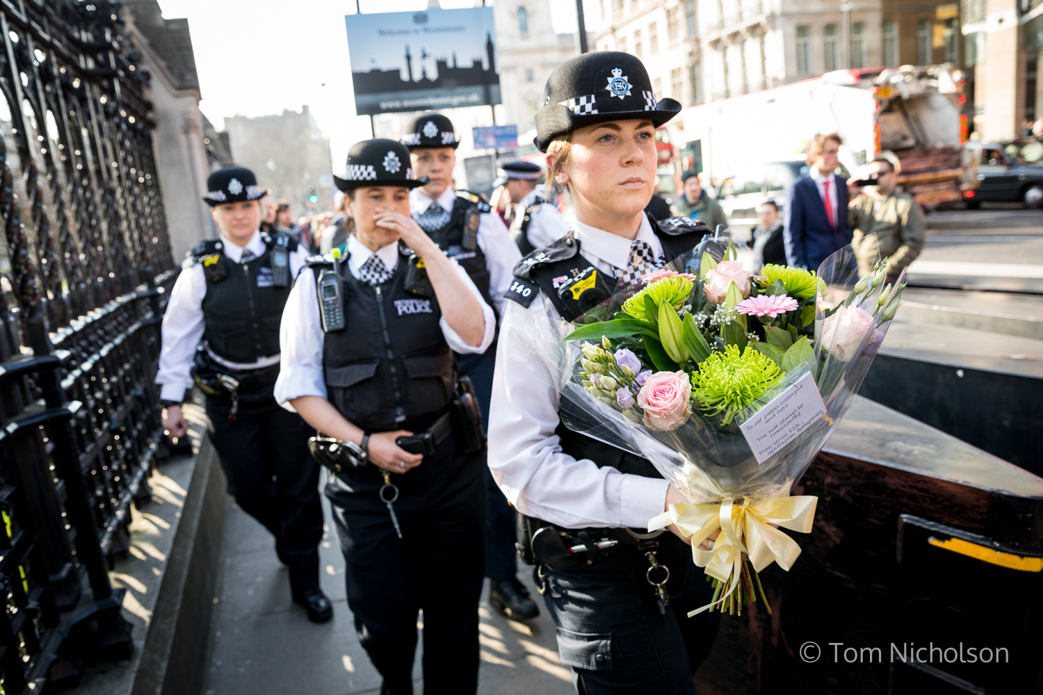 ©2017 Tom Nicholson. 24/03/2017. London, UK. Police officers leave flowers outside the Houses of Parliament in memory of those lost in the terror attack in London on 22 March.