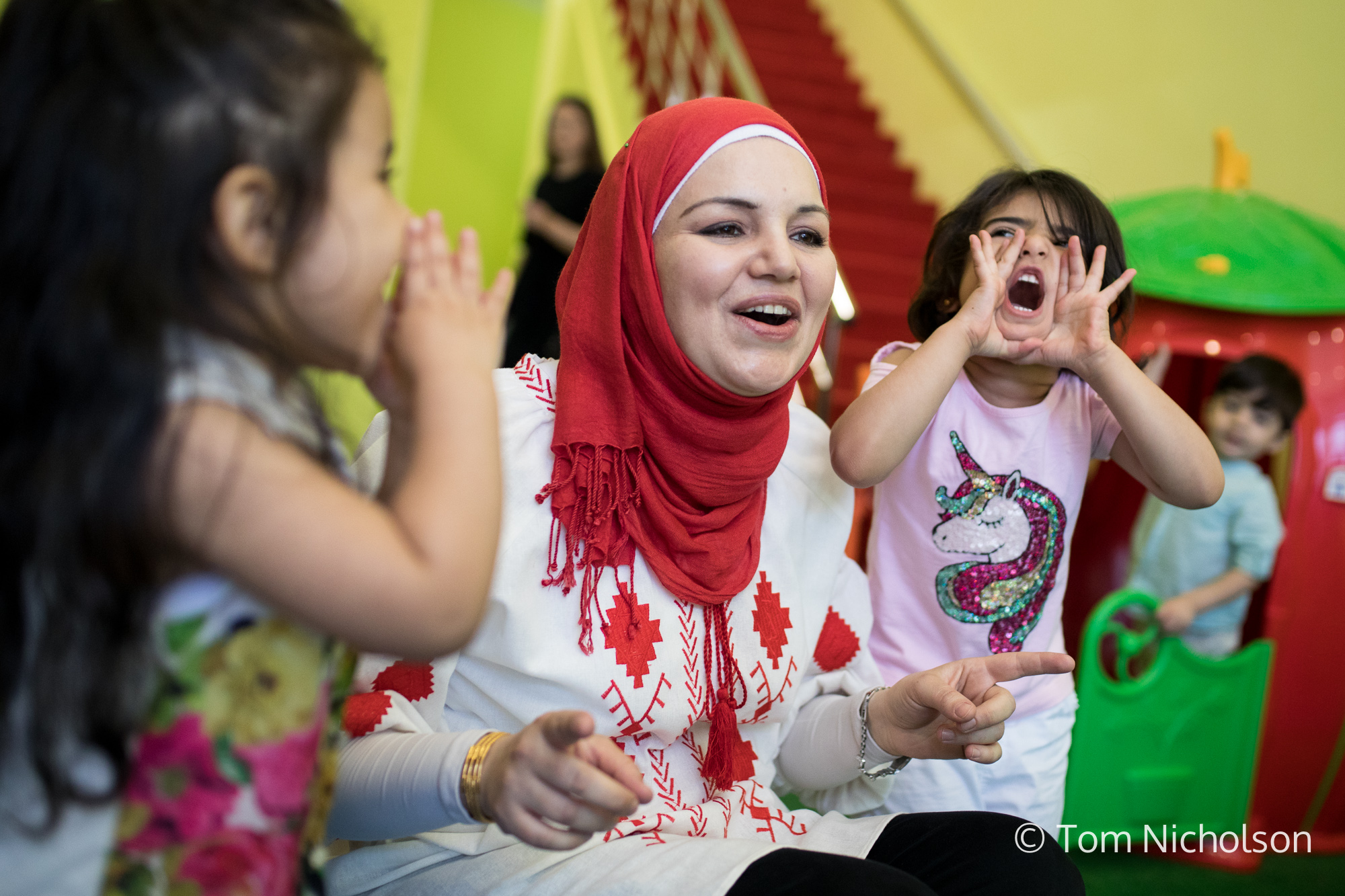 ©2018 Tom Nicholson. 03/07/2018. Gaziantep, Turkey. Dania Al Bouchi, (centre) age 30, from Hama, Syria, runs a Kindergarten in Gaziantep, Turkey with her husband Ahmad Al Bouchi. The pair moved from Deraa, Syria in 2013, expecting the conflict to be solved in one to two years, but haven't seen their loved ones for over six years. After moving to Turkey, Dania started studying Turkish but struggled as she had nowhere to leave her children. She then started her own Kindergarten, employing Syrian women as staff. Using her background in civil engineering, she designed the building and also the business' branding. Any children are welcome to the Kindergarten, and Dania hopes it will encourage Syrian mothers to be able to work or study whilst their children are safely looked after.