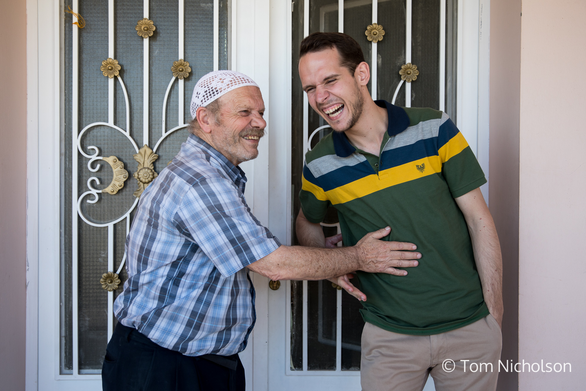 ©2018 Tom Nicholson. 20/06/2018. Bekaa Valley, Lebanon. Abdullah Birakdar, age 24, from Damascus, Syria, jokes with his father at their home in the Bekaa Valley, Lebanon, only a few kilometres from the Syrian border. Abdullah left Damascus with his family in 2013 to avoid serving in the army, and now teaches traditional Arab folk music at the Action for Hope centre. Abdullah's father used to be an Archaeologist at Damascus museum, where he made drawings of artefacts that had been excavated, to be kept as records. He recalled stories of successfully reassembling 17 pieces of an ancient column from Palmyra.
