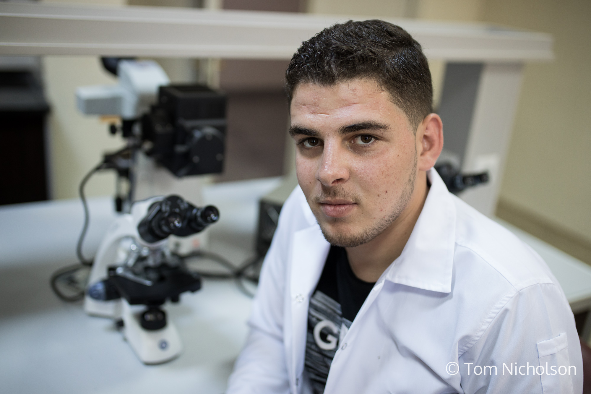 """©2018 Tom Nicholson. 02/07/2018. Kahramanmaraş, Turkey. Abdulaziz Omar, 20, from Aleppo, Syria, is studying Laboratory Analysis at at at Sütçü Imam University, Kaharamarmas. Abdulaziz's friend was injured in the war, and the village he was from had no doctors. He """"witnessed a lot of pain, blood and massacres in Syria"""", which lead to a dream to become a doctor, made possible by a SPARK scholarship. Abdulaziz wants to help people, and believes things will get better. He is open to the idea of returning to Syria despite the stigma attached to people who left and then returned."""
