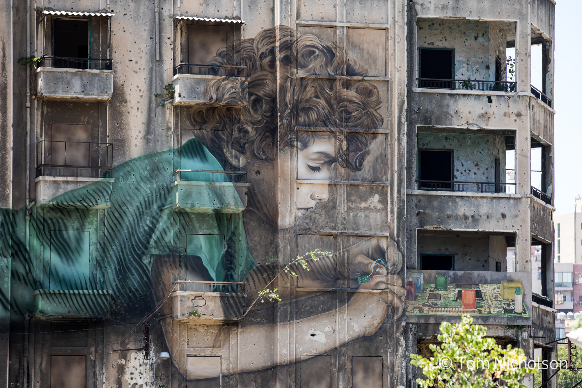 ©2018 Tom Nicholson. 22/06/2018. Beirut, Lebanon. Graffiti artwork by Jorge Rodriguez-Gerada is seen on the side of a building pocked marked by gunfire during the Lebanese civil war from 1975-1990.