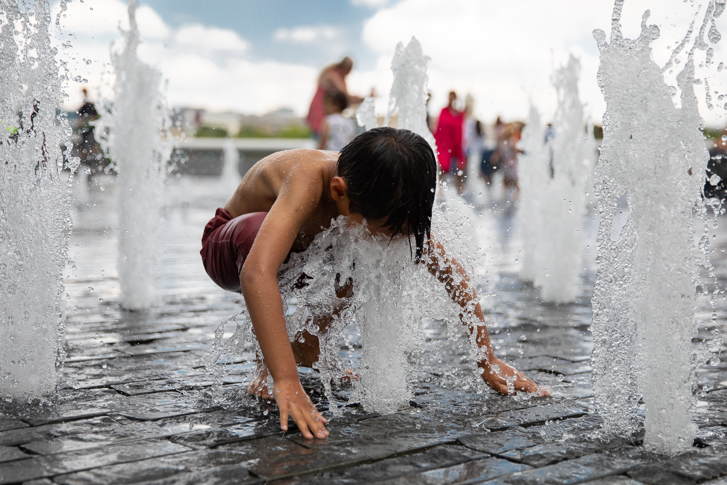 A child cools off in a fountain near London Bridge during hot weather in the capital. July 2018 - London, UK