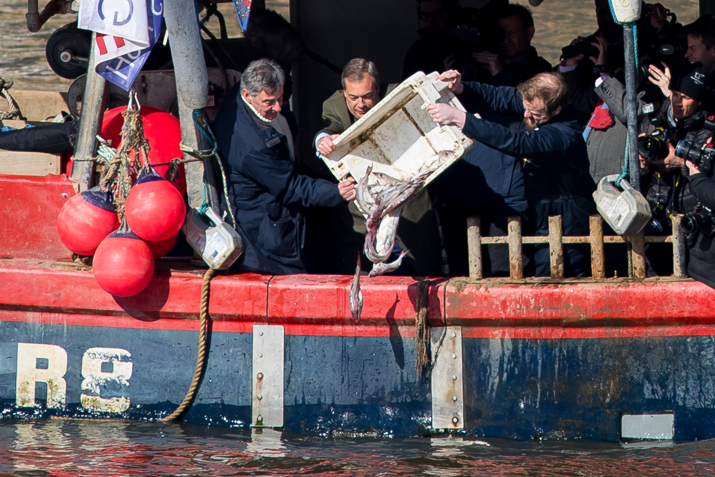 Nigel Farage (centre) joins campaigners from the 'Fisherman for Leave' group on a boat in the river Thames. They discarded dead fish into the river as a protest against yesterday's announcement that Britain will effectively continue to be involved in the EU's Common Fisheries Policy. The majority of fishermen voted for Britain to leave the EU. March 2018 - London, UK.