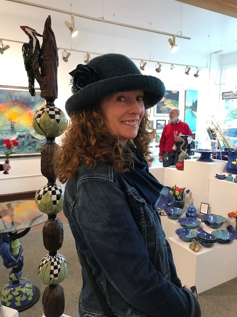 Cay, a Fort Bragg local, posing with her new purchase from our newest artist and designer of hats: Tess McGuire.