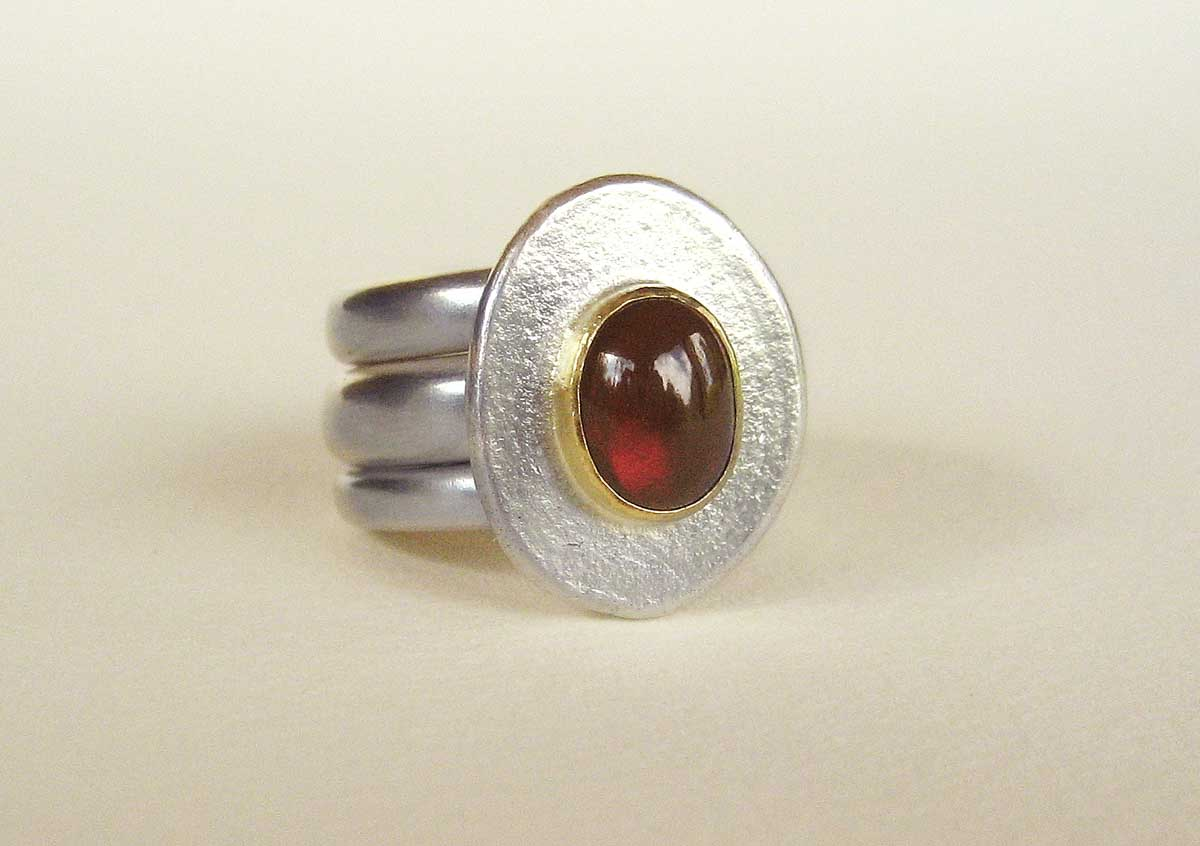 Silver ring with a garnet set in 18ct. gold