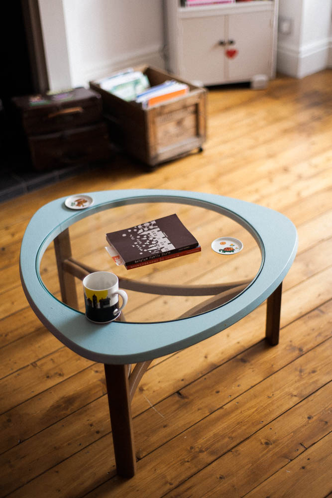 A Vintage coffee table with a glass top in a room with a natural wooden floor.