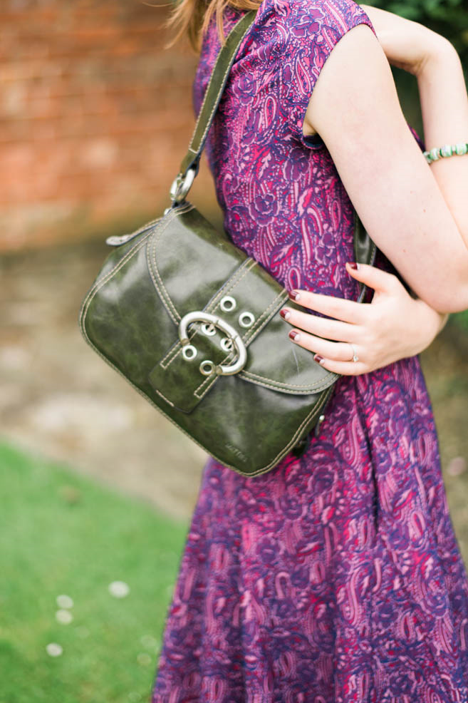 A Young Woman Holding A Green Leather Handbag