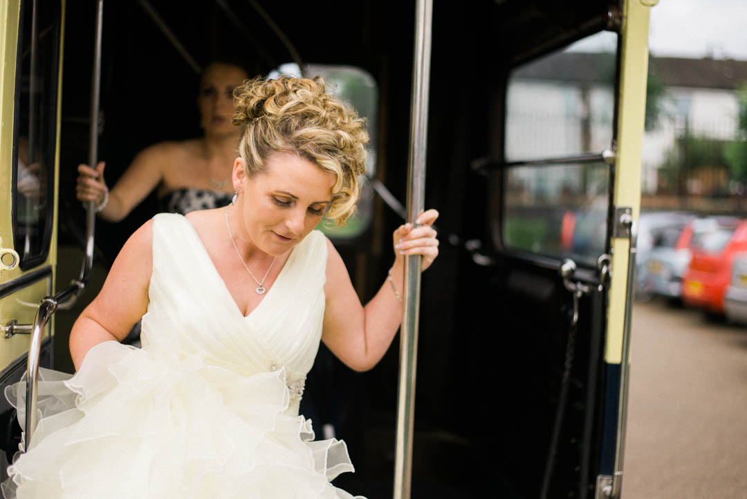 The Bride steps off an old school bus at Ordsall Hall Wedding Venue