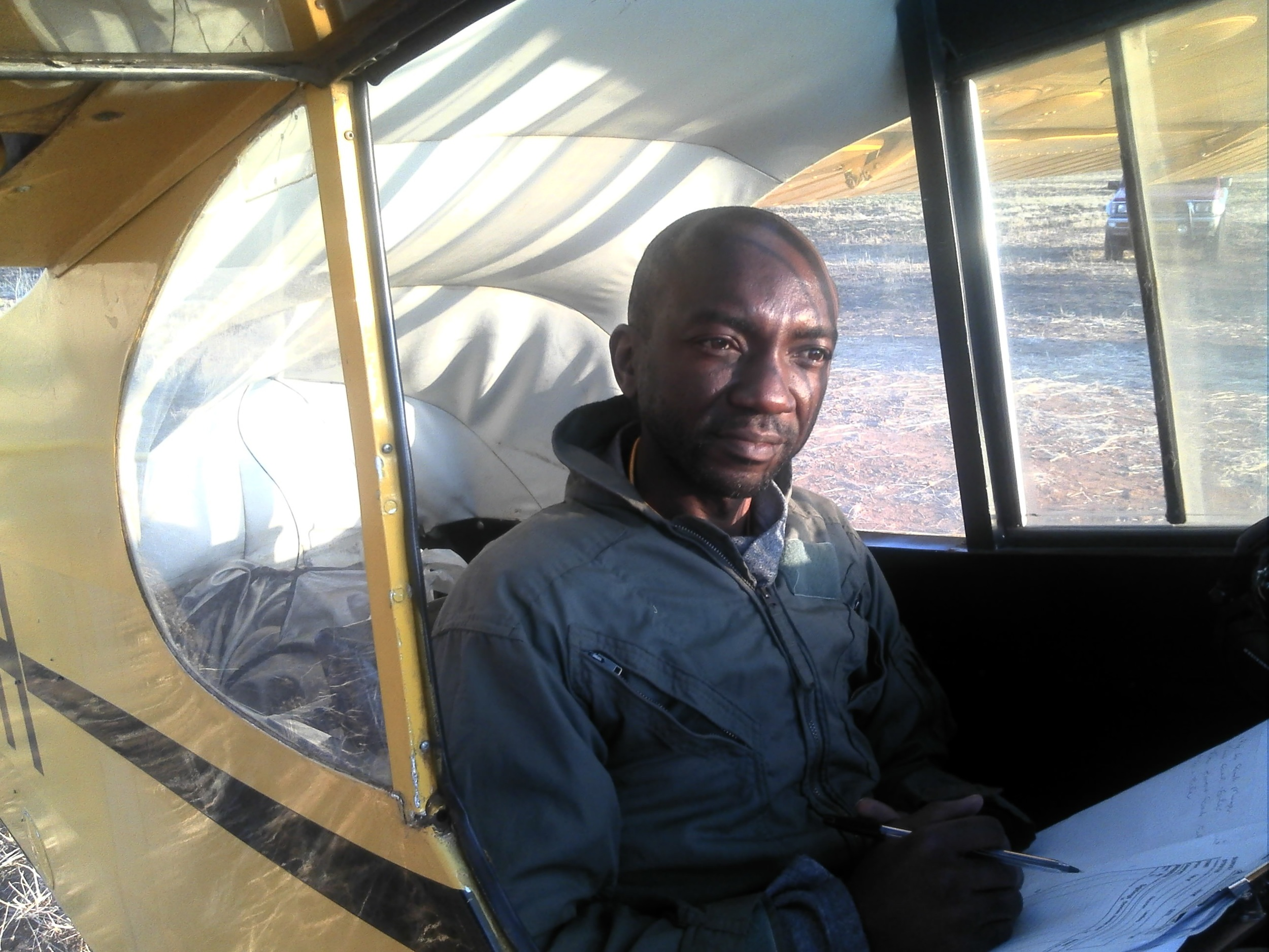 Senior Ecologist Greg Nyaguse of ZimParks prepares for take-off as the recorder/observer in the tiny Supercub aircraft used to conduct block counts in the hills of the Zambezi escarpment.  Makuti, July 2014
