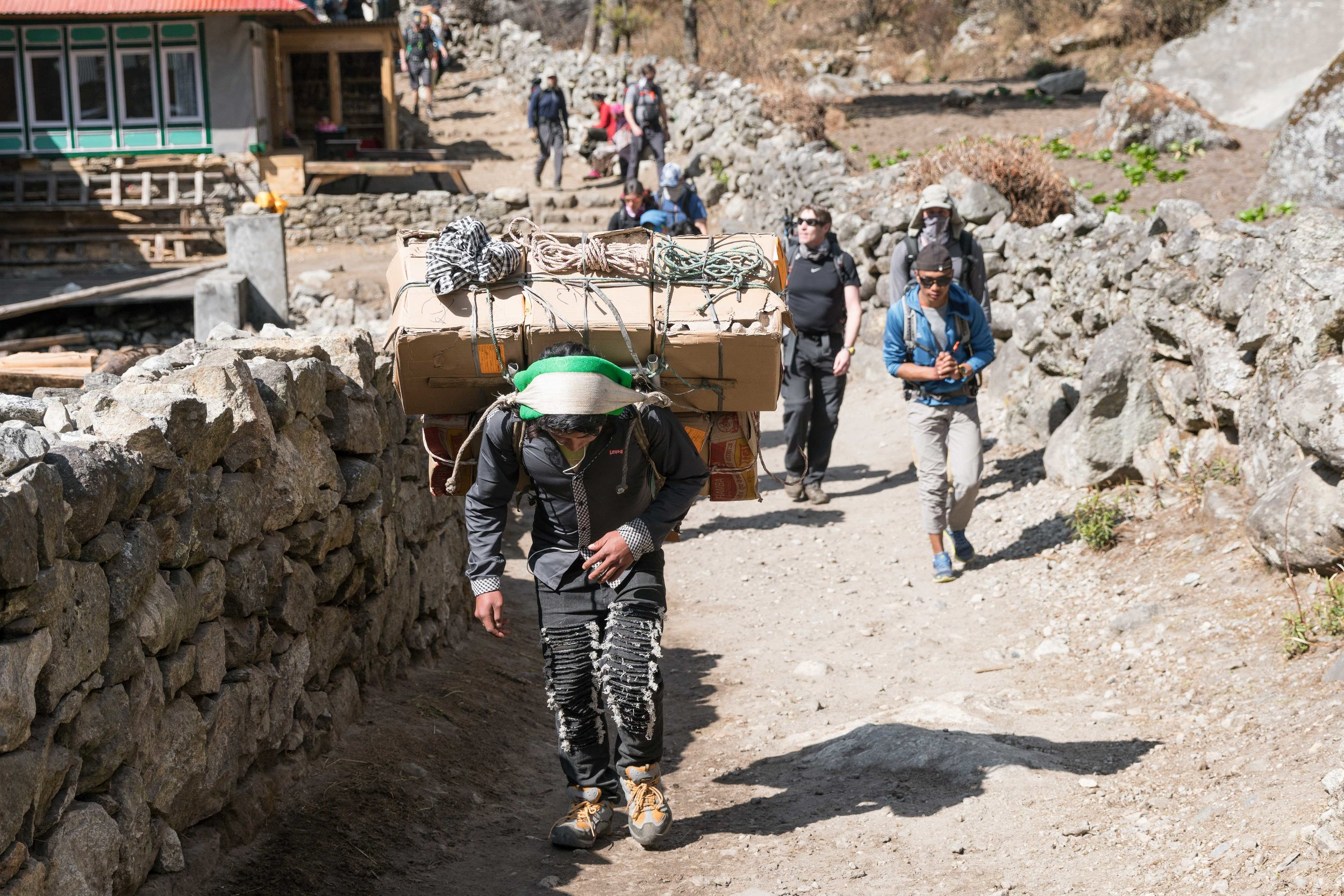 A porter carries goods along the trekking route between Lukla and Namche Bazar