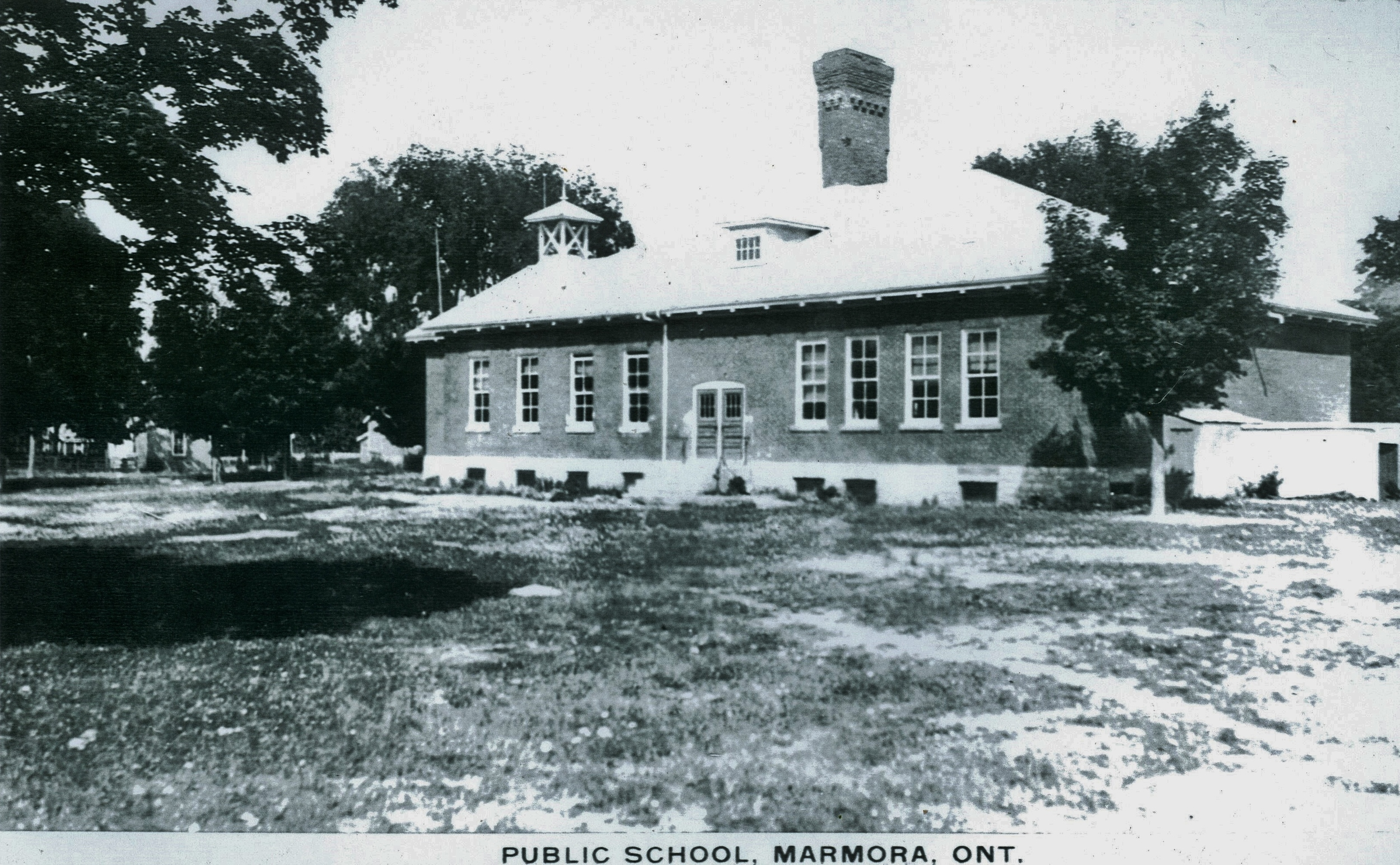 In 1915 the original structure (see above ) burned and this building was constructed from the remains of the first floor. Note school bell and large chimney. Photo taken before extension built.
