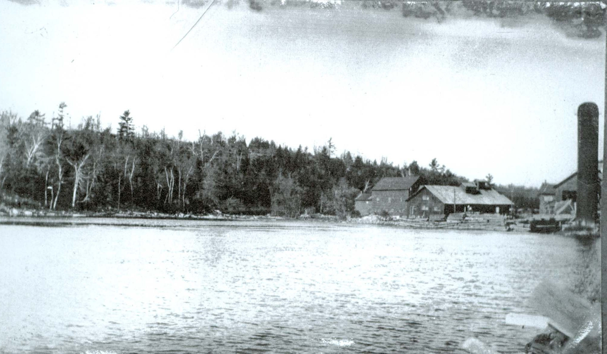 Photo of Pearce Mills constructed on what is now the dam location. Visible is the west shore of Crowe River.