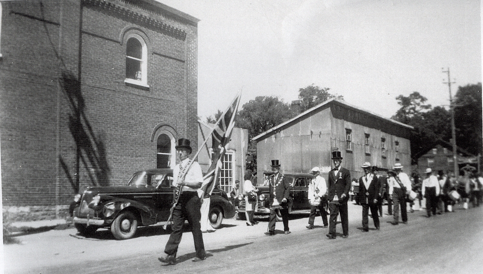 July 12th parade with Charles Dunlay in the lead,, on the now #7 highway, heading west. The Brick building is the O'Neill building which later become the TD Bank in Marmora. In the centre is tne blacksmith shop of Charles Sr. & Eli Clairmont. Far right the Clairmont house is visible. This house was later moved north, opposite the Town Hall (11 Bursthall St)