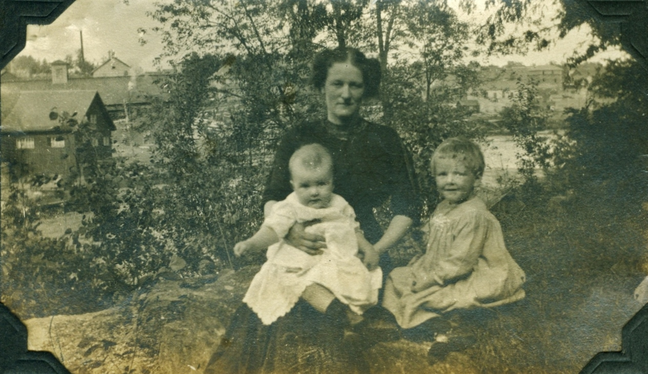 """Mrs. MacKechnie with """"Jean"""" born 1910 and """"Marjorie"""" born 1909 Photo appears to have been taken on west side of river opposite pearce mills. note pearce grist mill still standing."""