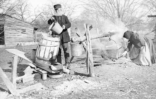 Recollections of domestic life. Soap making,  1884. The farmer is pouring water into the ash barrel to make lye; his wife is boiling a kettle of fat. Lye and fat produce soft soap.