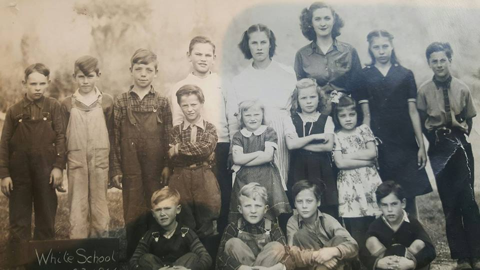 """White School 1946. Back row - 4th boy to the right John """"Jack"""" Clemens, Dorothy Hulsmans, teacher, unknown girl, Leo Hulsmans (my dad) at the end standing. 2nd row boy standing: David Hulsmans, beside him Jean Hulsmans. Front row sitting 3rd boy Henry Hulsmans."""