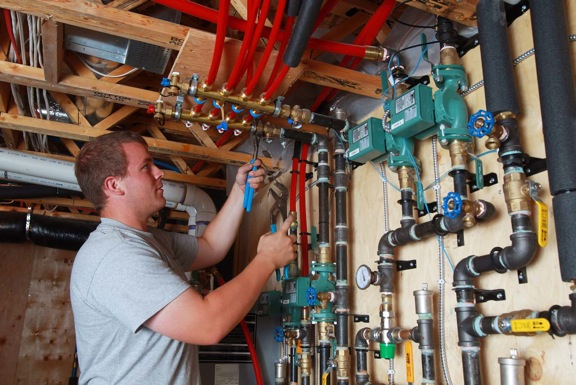Brent McRoberts makes a final connection on a brass manifold to prepare for the startup of the new in-floor heating system.