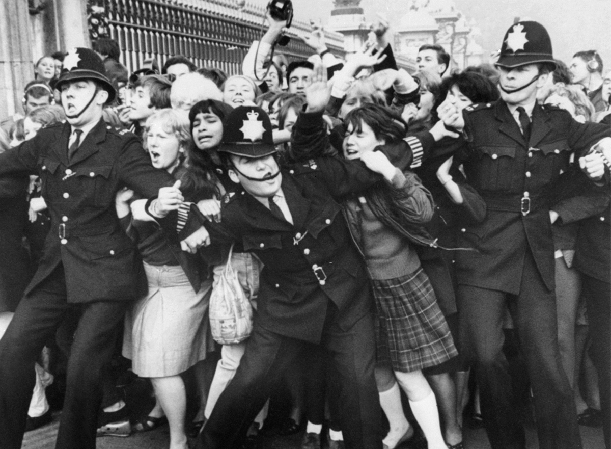 Beatles fans try to break through a police line at Buckingham Palace in London in 1965