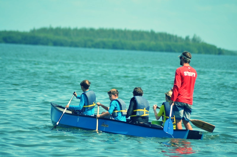 Calusa campers canoe in San Carlos Bay with counselor Mike.