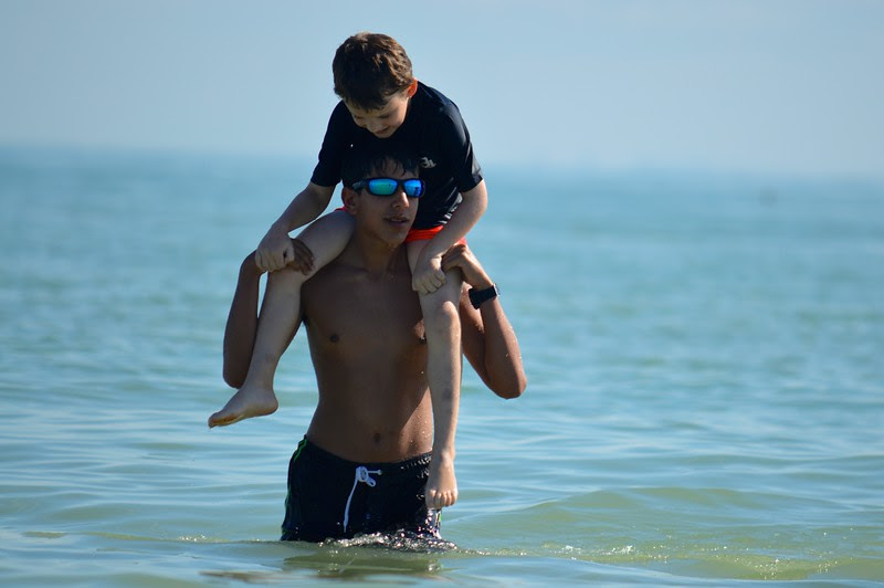 Counselor-In-Training Jivan Khakee gives one of his campers a lift to the beach.